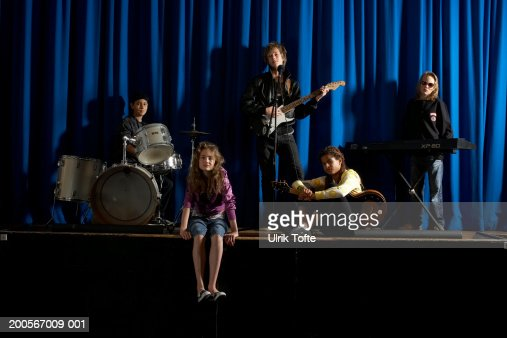 Group of boys and girls (12-14) on stage in assembly hall, boys playing instruments