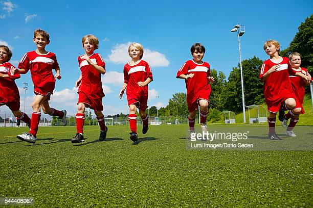 Group of boys at soccer training, running side by side, Munich, Bavaria, Germany
