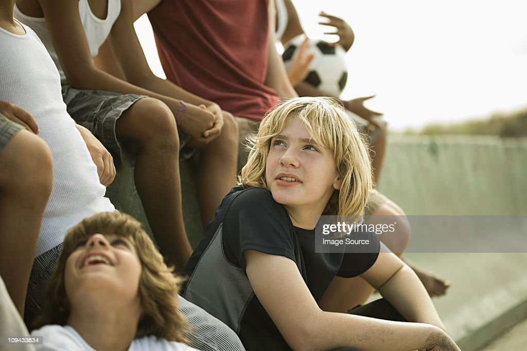 Group of boys by wall with football : Stock Photo