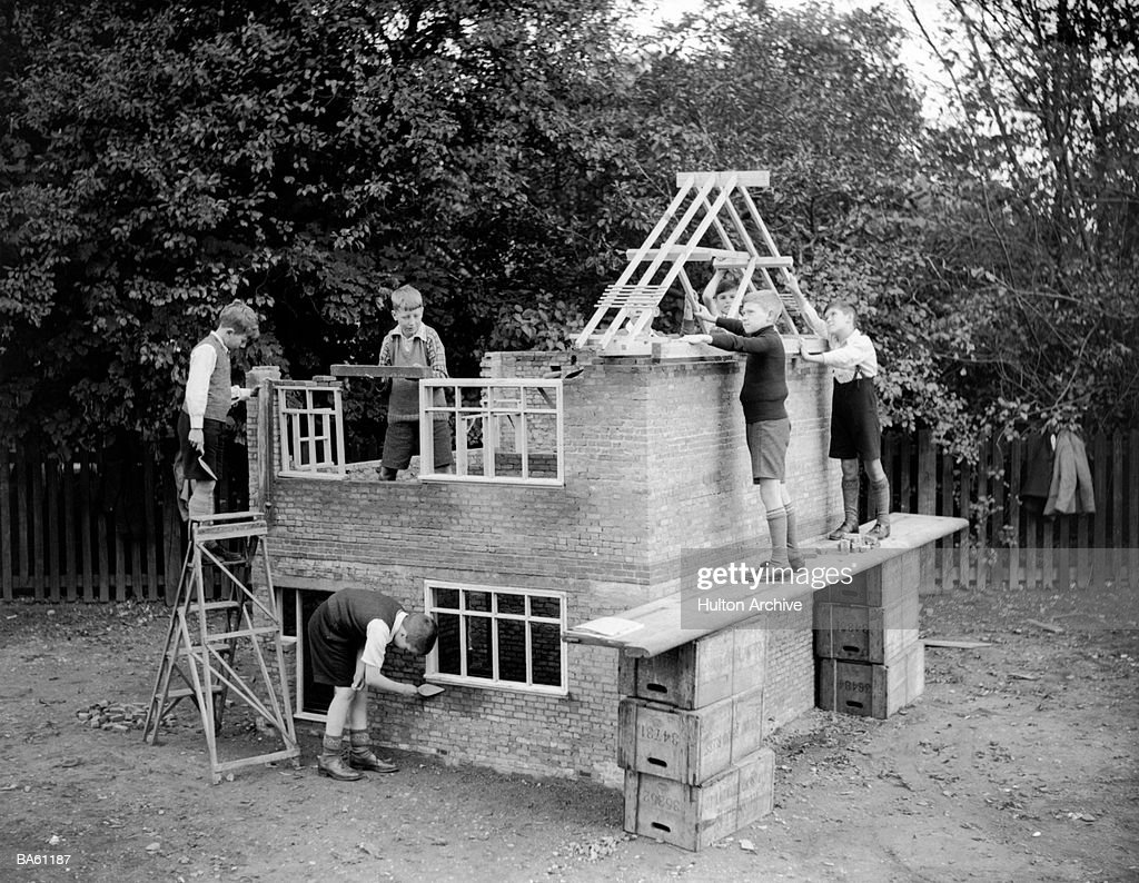 Group of boys (7-9) constructing miniature house (B&W) : Stock Photo