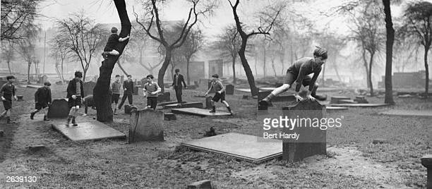 A group of boys from the Gorbals play amongst the gravestones of the Corporation Burial Ground in Rutherglen Road one of the few areas of greenery in...