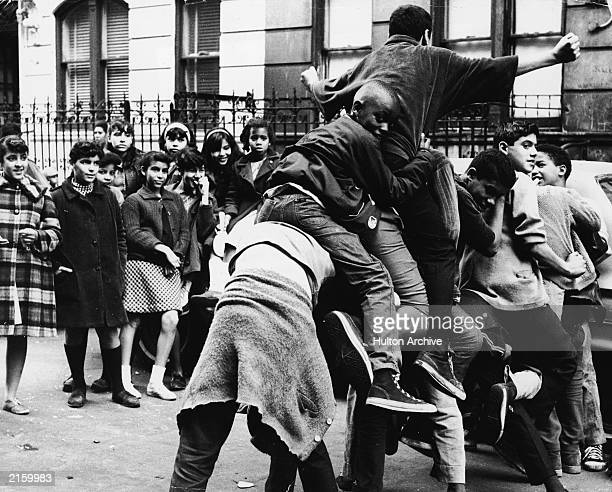 A group of boys pile on top of each other as a group of girls look on New York city New York circa 1970