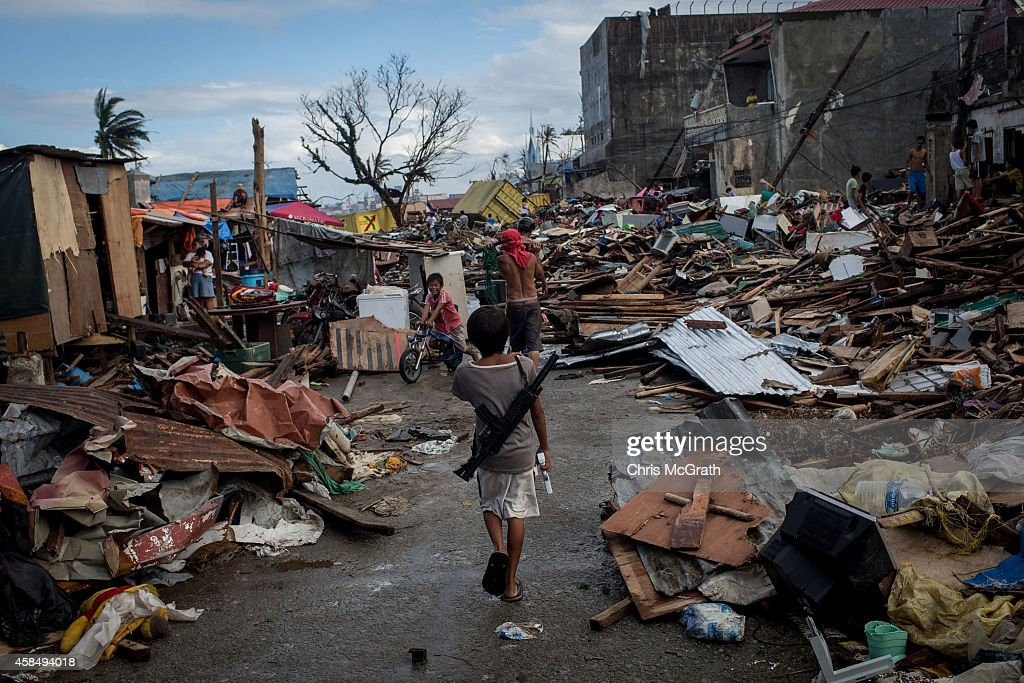 A group of boys play with replica guns amongst debris in Tacloban City following the recent super typhoon on November 17 2013 in Leyte Philippines...