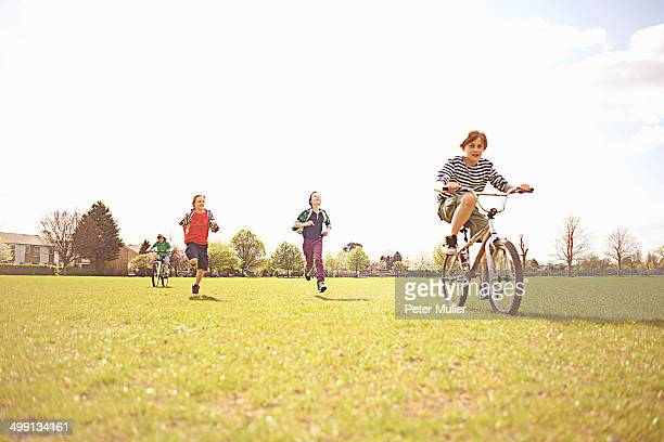 Group of boys running and cycling on playing field