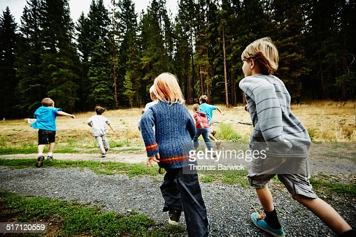 Group of boys running out to field at summer camp : Stock Photo