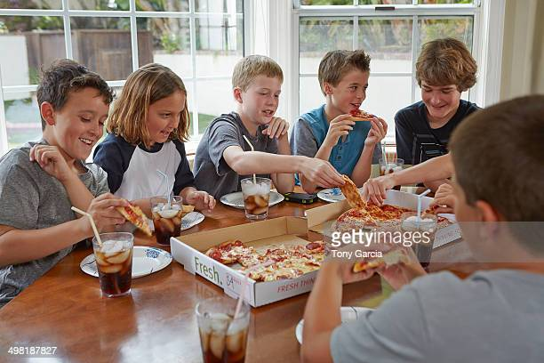 Group of boys sharing pizza