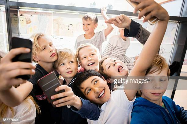 Group of boys taking selfie in corridor