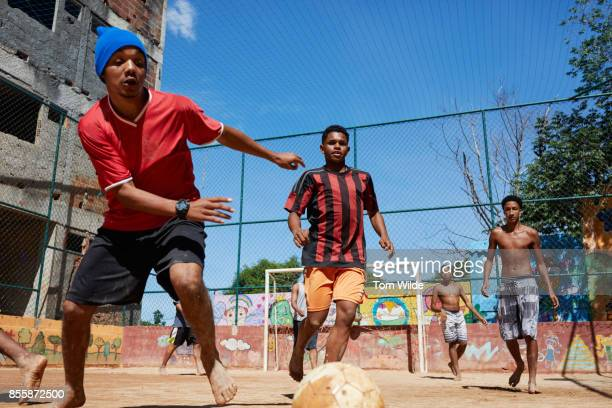 Group of Brazilian boys playing football on a dirt court in Rio de Janeiro
