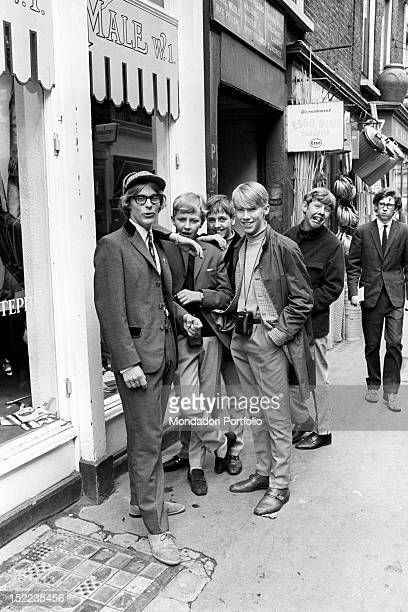 A group of British young mods posing outside John Stephen's clothes shop One of them wears a jacket in the Edwardian style and a hat in the Sherlock...