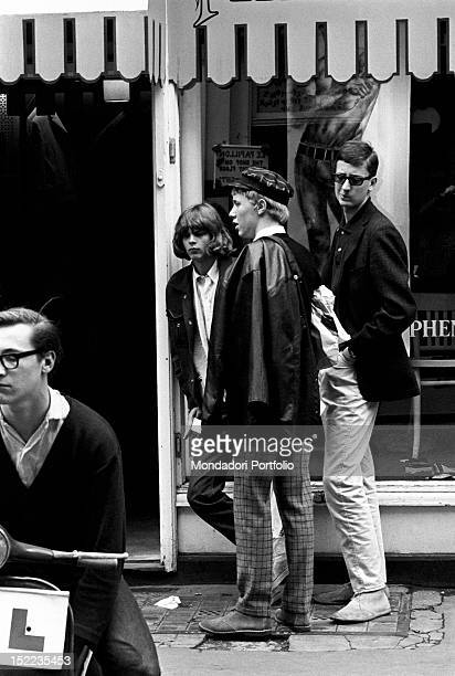 A group of British young mods waiting outside John Stephen's clothes shop They wear Clarks shoes tartan trousers leather jacket and hats in the...