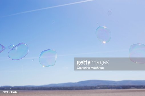 A group of bubbles float through blue skies : Stock Photo