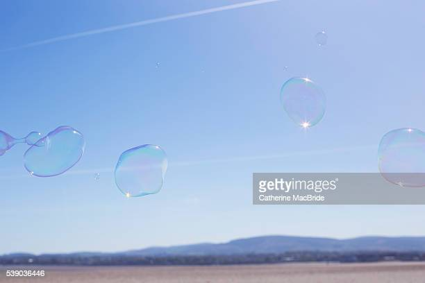 A group of bubbles float through blue skies