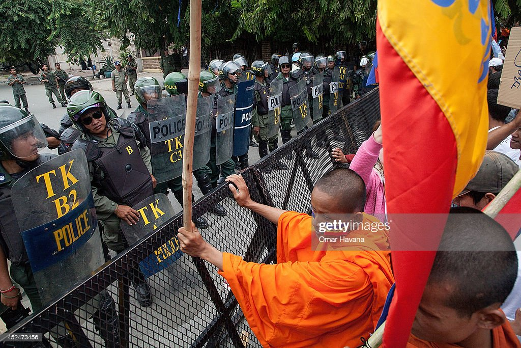 A group of Buddhist monks and demonstrators stand in front of the barricades set up to impede access to the Vietnamese Embassy on July 21, 2014 in Phnom Penh, Cambodia. Thousands of protesters and monks march through the streets of Phnom Penh to deliver petitions to the French, British, American, Russian and Chinese embassies, before arriving at the Vietnamese Embassy. The protesters, organised by the Federation of Cambodian Intellectuals and Students (FCIS) and leaders of the Khmer Krom community, are demanding an apology from Vietnamese Embassy First Counsellor Tran Van Thong, who recently said that the former Kampuchea Krom provinces were held by Vietnam before their occupation by France. Ahead of the protest, Phnom Penh municipal authorities banned the protest, threatening the protesters who defied the ban could be jailed for up to 15 years.