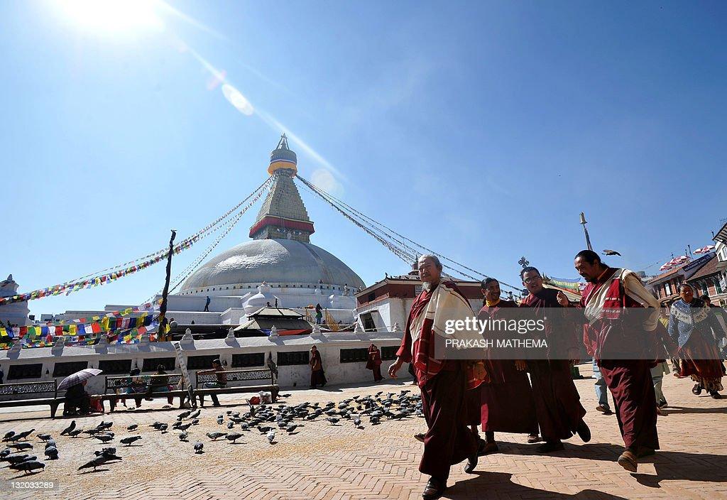 A group of Buddihst monks walk past the Boudhanath Stupa on the outskirts of Kathmandu on November 10 2011 A Tibetan exile chanting antiChina slogans...