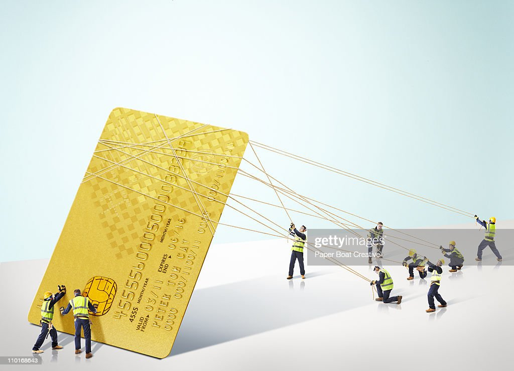 Group of builders carrying a giant credit card : Stock Photo