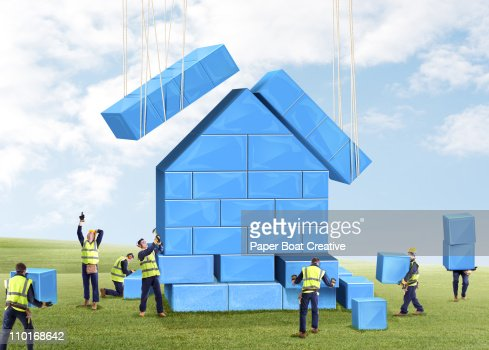 Group of builders putting together a toy house : Stock-Foto