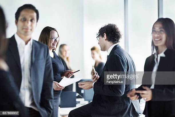 Group of business colleagues talking together in office