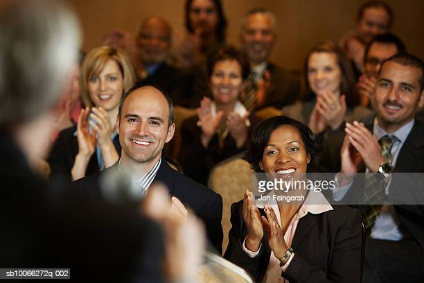 Group of business executives applauding at conference centre, smiling