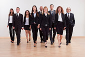 Large diverse group of business executives approaching walking towards the camera led by a smiling woman