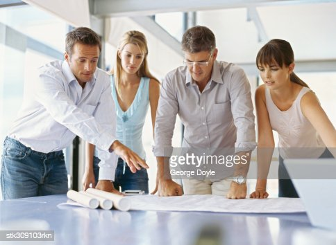 group of business executives looking at a blueprint in an office : Stock Photo