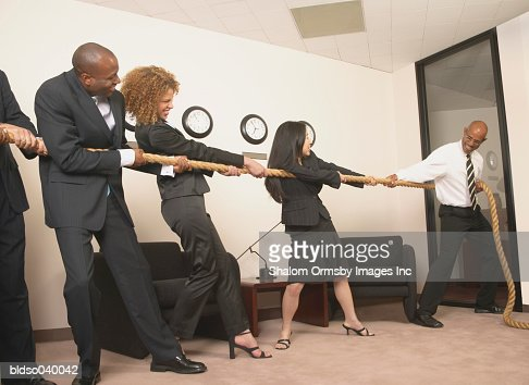Group of business executives playing tug of war in the office : Stock Photo