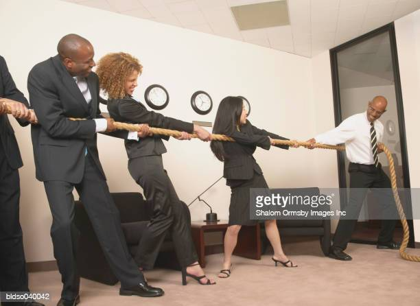 Group of business executives playing tug of war in the office