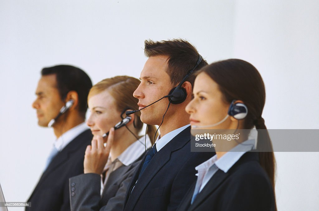 Group of business executives standing in a row wearing headsets : Stock Photo