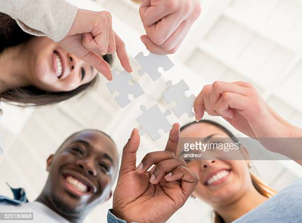 Group of business people assembling a puzzle