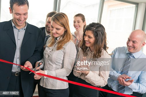 A group of business people at an ribbon cutting ceremony
