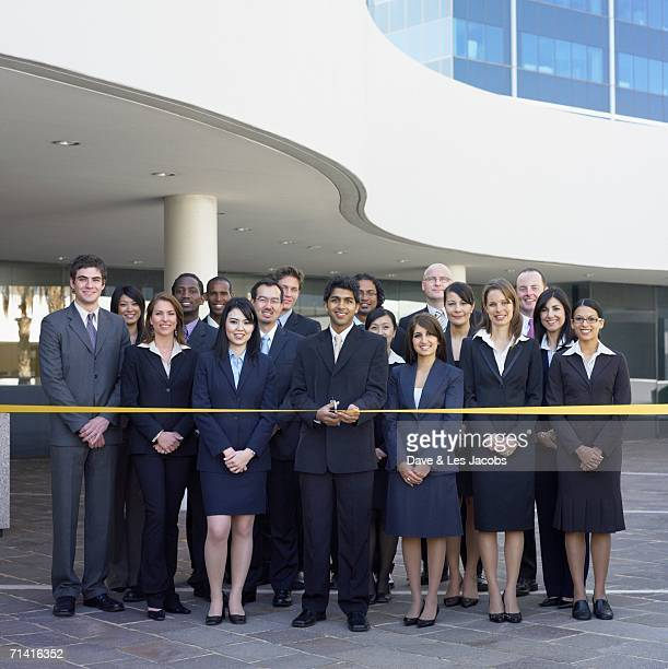 Group of business people behind yellow tape