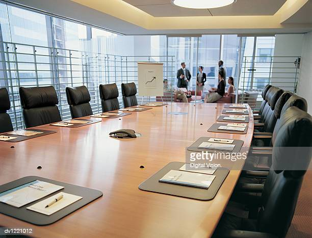 Group of Business People Discussing a Business Plan in a Distant Office with a Conference Table in the Foreground