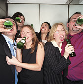 Group of business people drinking beer in lift, close-up