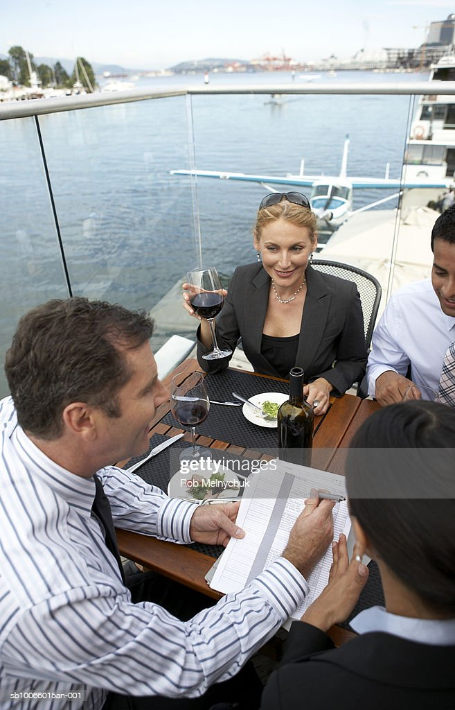 Group of business people eating and reading documents outdoors : Stock Photo