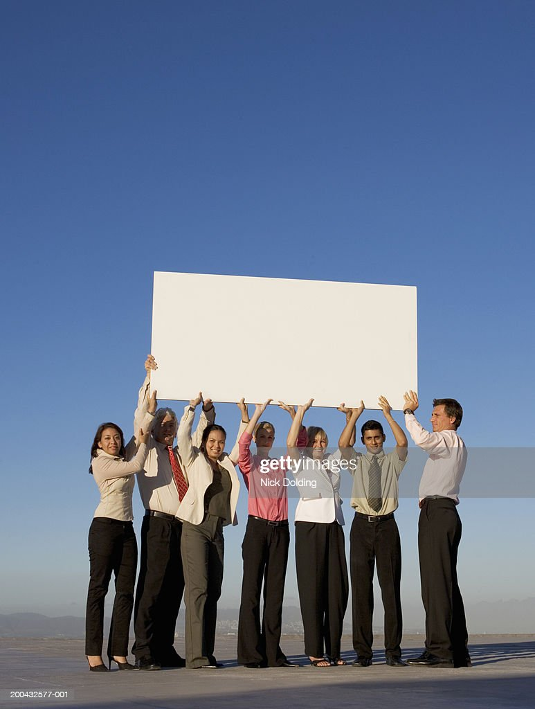 Group of business people holding a blank board on roof : Stock Photo