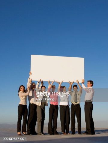 Group of business people holding a blank board on roof : Bildbanksbilder