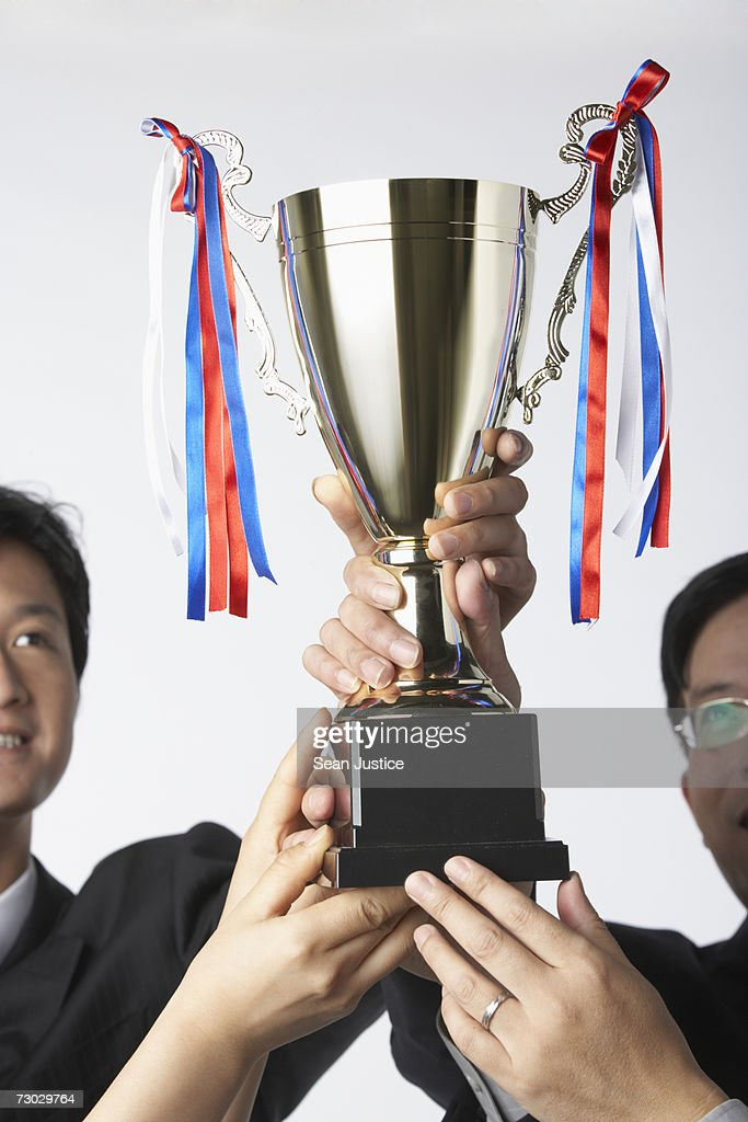 Group of business people holding trophy, close-up : Stock Photo