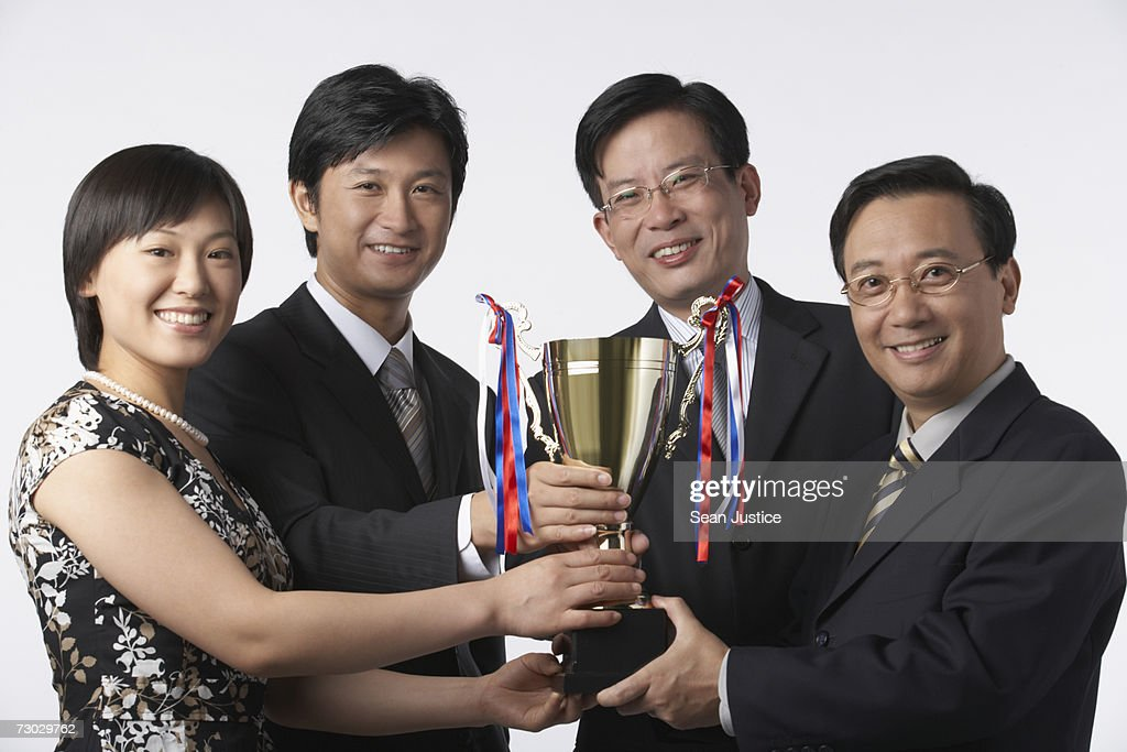 Group of business people holding trophy : Stock Photo