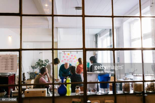 Group of business people huddled around table working