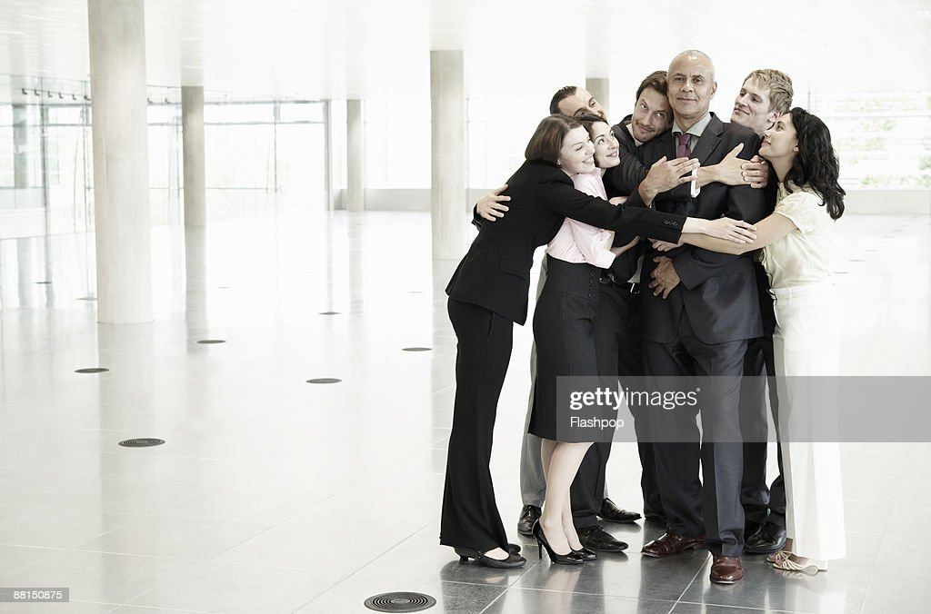 Group of business people hugging one person : Stock Photo