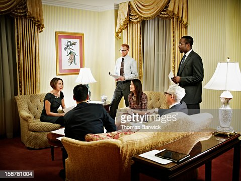 Group of business people in meeting in hotel suite : Stock Photo