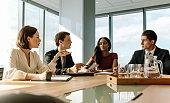 Female executive putting her ideas during meeting in conference room. Group of business people having meeting in a board room.