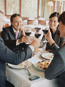 Group of business people raising glasses at restaurant table, smiling