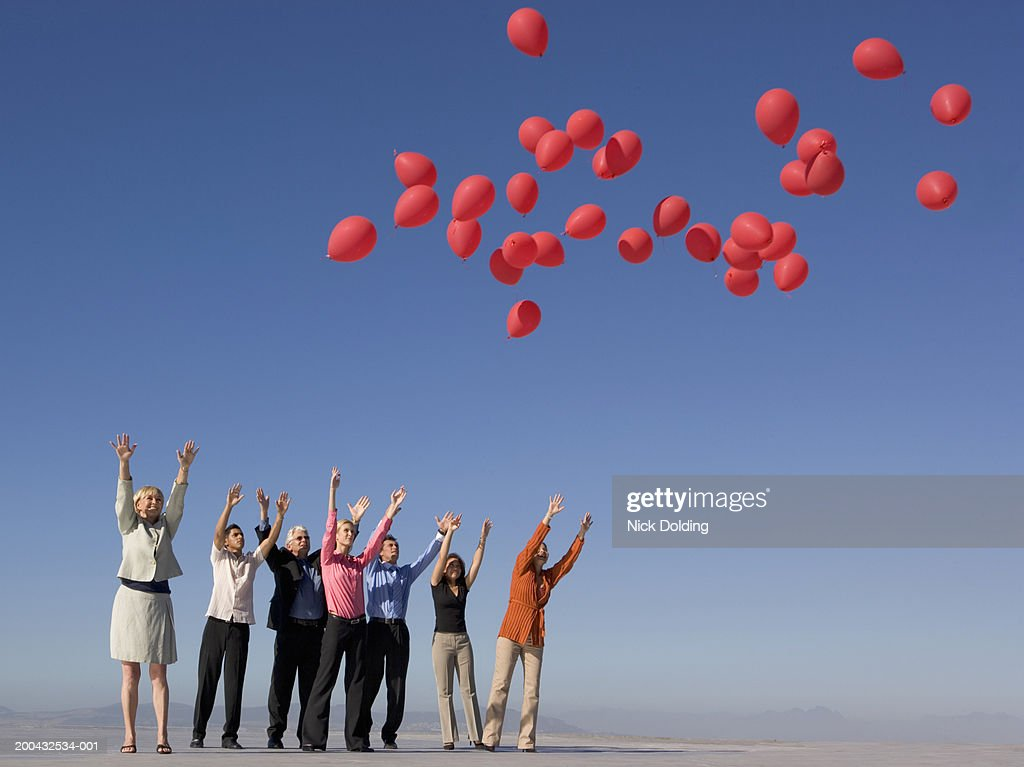 Group of business people releasing red balloons on roof