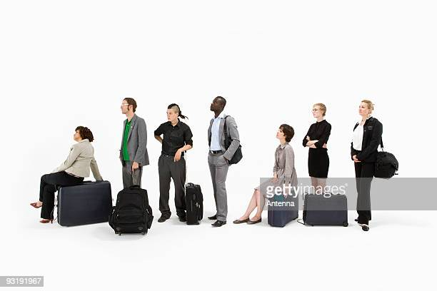 A group of business people standing in a line with luggage