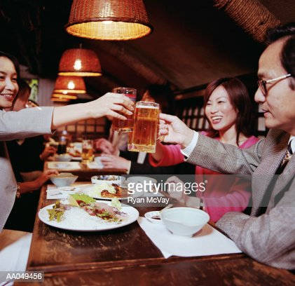 Group of business people toasting mugs of beer over dinner : Stock Photo