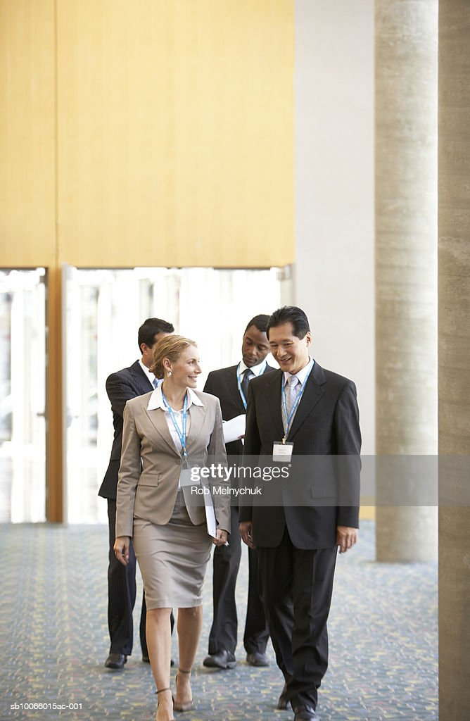 Group of business people walking down hallway : Stock Photo