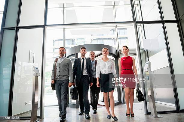 Group of business people walking into glass office building