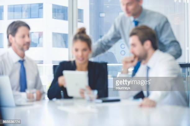 Group of business people with digital tablet. There are 3 men and a woman.