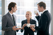 Group of businessmen having tea in office after meeting, provide good employment conditions for employees, co-working space, surrounding with right people. Enjoy coffee break concept. Focus on woman