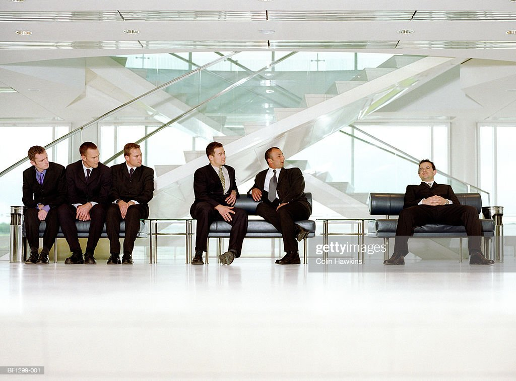Group of businessmen in waiting area watching relaxed man : Stock Photo